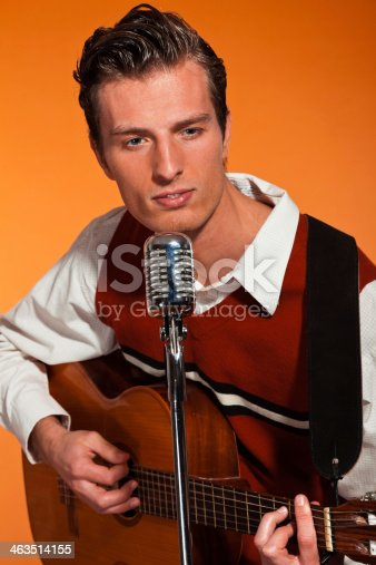 463242403 istock photo Retro fifties rock and roll singer playing accoustic guitar. 463514155