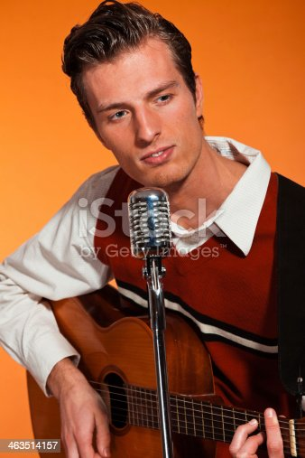 463242403 istock photo Retro fifties rock and roll singer playing accoustic guitar. 463514157