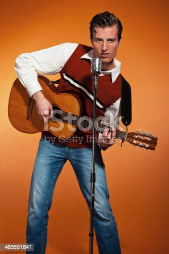 463242403 istock photo Retro fifties rock and roll singer playing accoustic guitar. 463551841