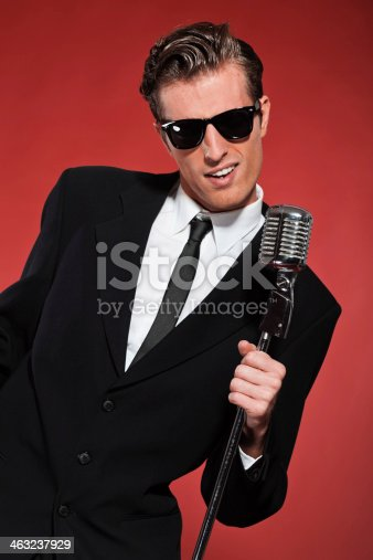 463242403 istock photo Retro fifties singer with vintage microphone and sunglasses. 463237929