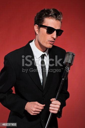 463242403 istock photo Retro fifties singer with vintage microphone and sunglasses. 463237933