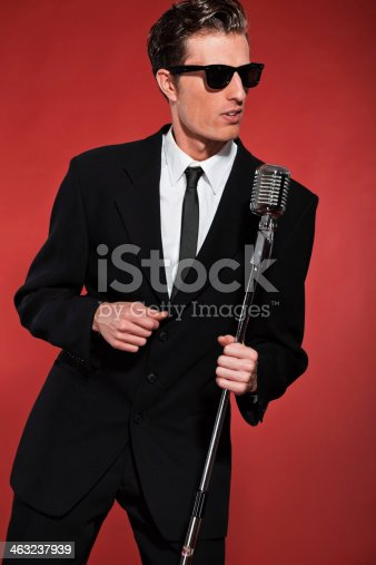 463242403 istock photo Retro fifties singer with vintage microphone and sunglasses. 463237939