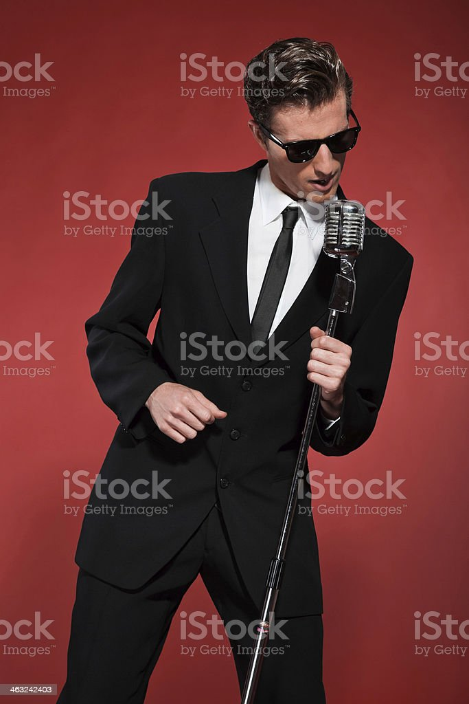 Retro fifties singer with vintage microphone and sunglasses. stock photo