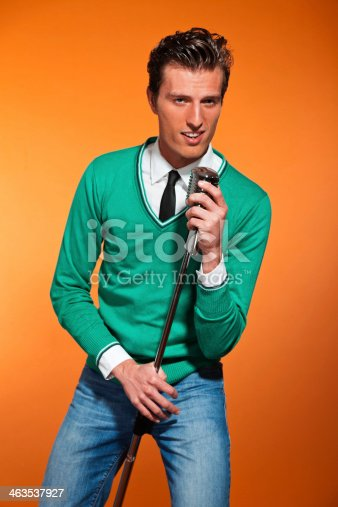 463242403 istock photo Retro fifties style rock and roll singer with green shirt. 463537927