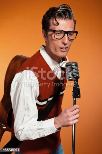 463242403 istock photo Retro fifties style rock and roll singer with vintage microphone. 463235971