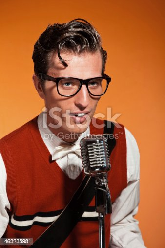 463242403 istock photo Retro fifties style rock and roll singer with vintage microphone. 463235981