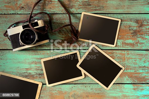 istock Retro film camera and instant paper photo 658829766