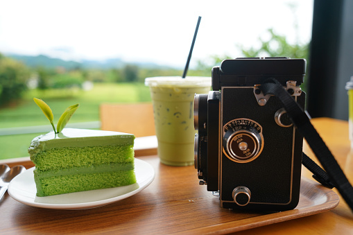 Retro film camera and green tea cake Lifestyle of the new generation in tourism