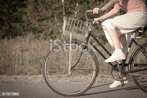 Color image of Retro Gal riding a vintage bicycle down a country road.