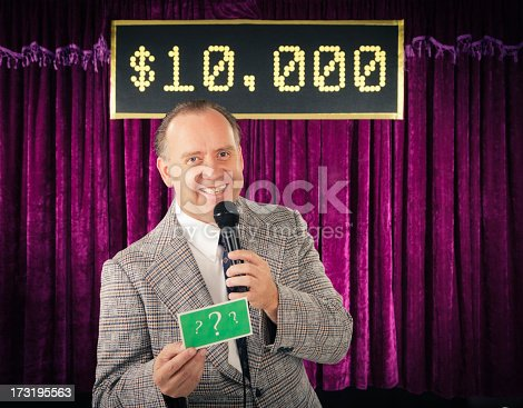 A retro color processed game show host holding a microphone. Photographed in studio with a purpose built set and props.