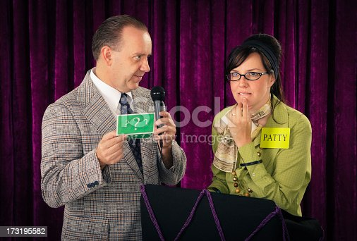 A game show host and contestant. Photographed in studio with a purpose built set and props.