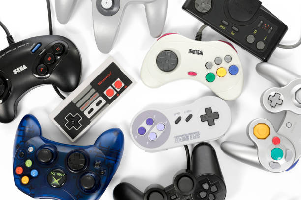 Retro Gaming Controllers Taipei, Taiwan - February 19, 2018: A collection of retro video game controllers shot from above on a white background. nintendo stock pictures, royalty-free photos & images