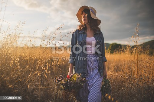 Lovely and gorgeous hipster girl with a basket full of flowers and a hat, traveling through a golden wheat field in a denim jacket.