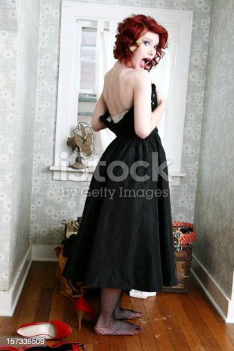 Retro girl in a bombshell black dress caught getting dressed
