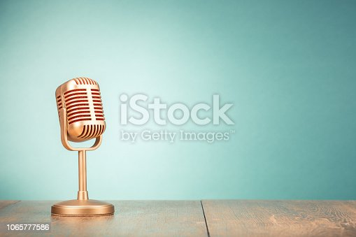 Retro golden microphone for press conference or interview on table front gradient mint green background. Vintage old style filtered photo