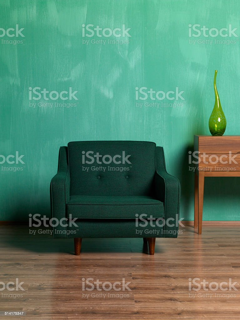 retro green armchair on green wall stock photo