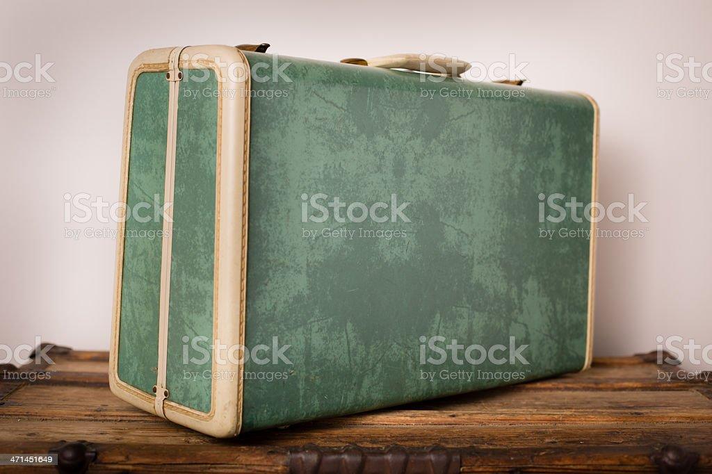 Retro, Green Suitcase Sitting on Wood Trunk stock photo