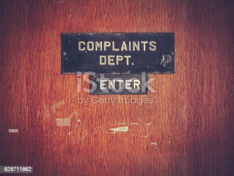 Retro Filtered Image Of A Grungy Complaints Department Sign On A Door