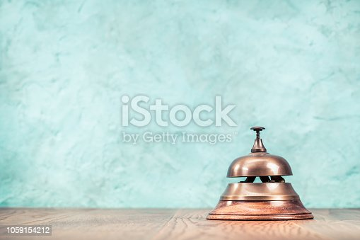Retro hotel reception service desk bell front textured aquamarine concrete wall background. Vintage old instagram style filtered photo