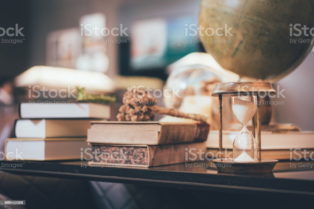 Retro hourglass blur stack of old books and world desk globe on retro hourglass blur stack of old books and world desk globe on wooden table gumiabroncs Image collections