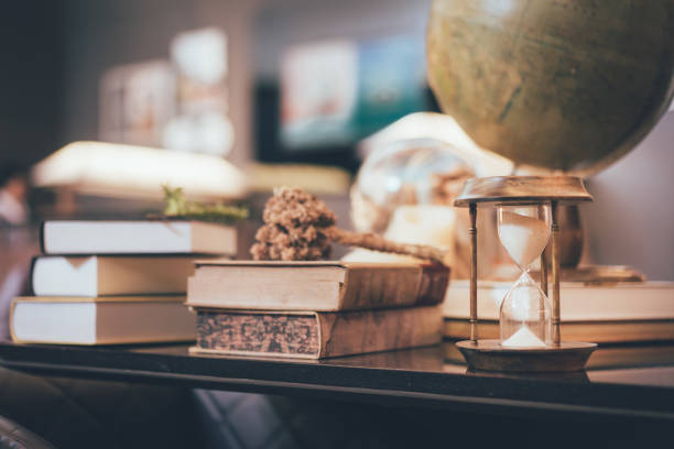 retro-sanduhr unschärfe stapel alter bücher und schreibtisch weltkugel auf hölzernen tisch, lernen und bildung konzepte. - schnell lesen lernen stock-fotos und bilder