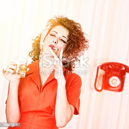 istock Retro house wife smoking and drinking  while ironing. 168615267
