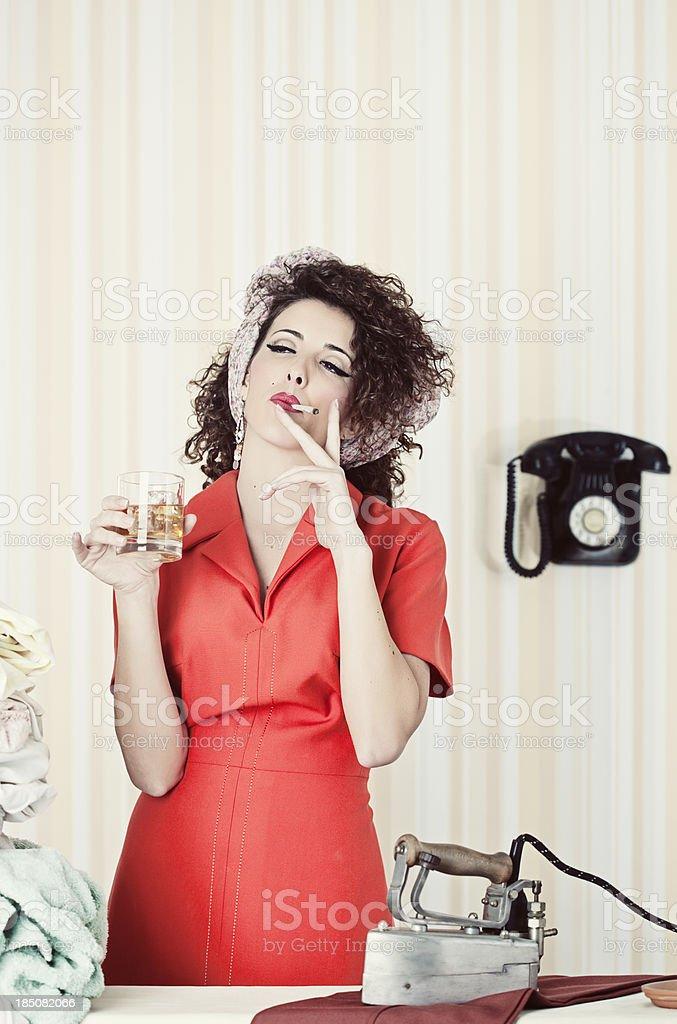 Retro house wife smoking and drinking  while ironing. royalty-free stock photo