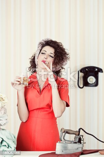 istock Retro house wife smoking and drinking  while ironing. 185082066