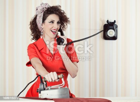 istock Retro house wife talking to the phone while ironing. 168615077