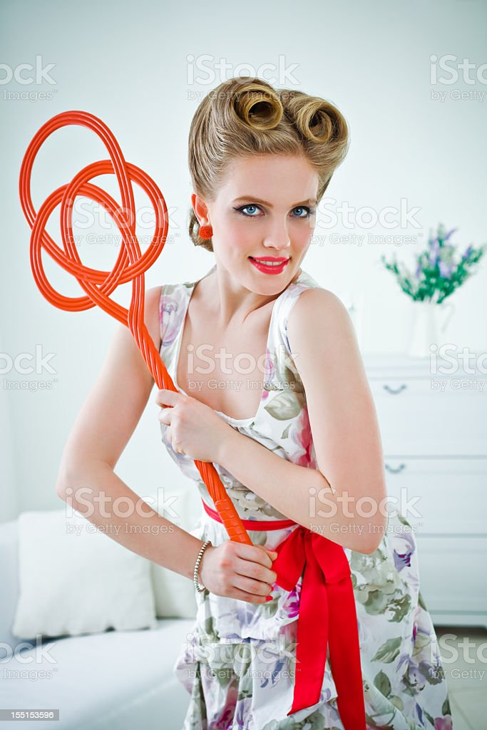 Retro housewife with carpet beater stock photo