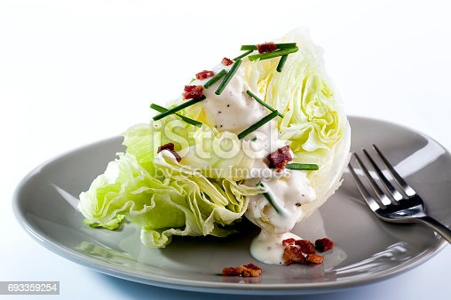 Wedge of iceberg lettuce with blue cheese dressing, bacon, and chives.