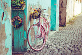 Pink vintage bike with basket full of flowers next to an old cyan building in Spain