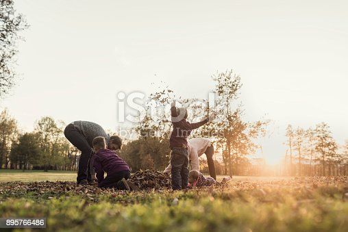 Retro image of family rejoicing in an autumn sunset throwing leaves in the air in nature backlit by the glow of the sun.