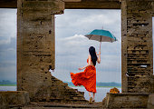 woman fashion dress standing on the retro old cottage house in the lake, holding umbrella under raining season