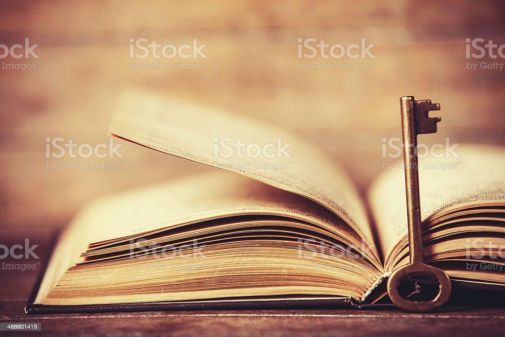 Retro key and opened book stock photo