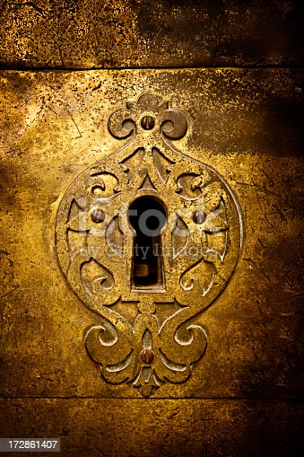 An old medieval keyhole on a gold / brass door with a rutsy ornate plate.