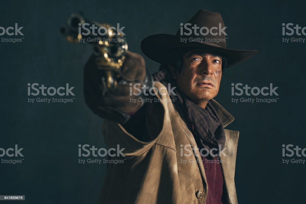 Retro late 1960s western actor. Shooting with revolver. stock photo