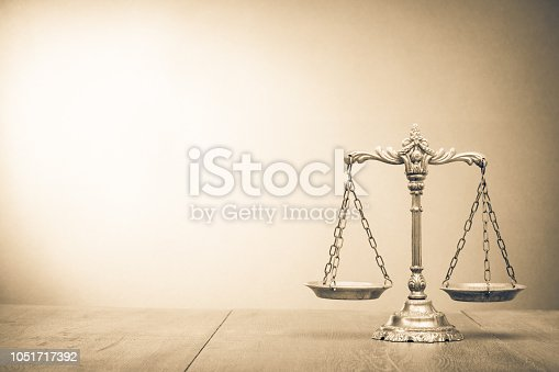 Retro law scales on table. Symbol of justice. Vintage style sepia photo