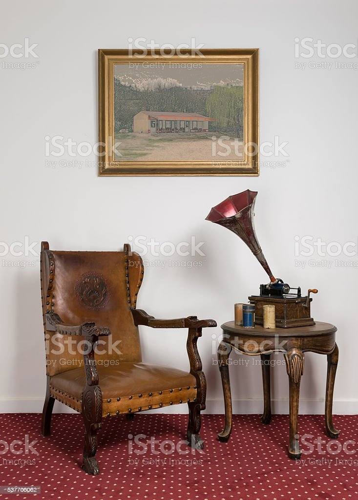 Retro leather armchair, old phonograph, cylinders on round coffee table stock photo