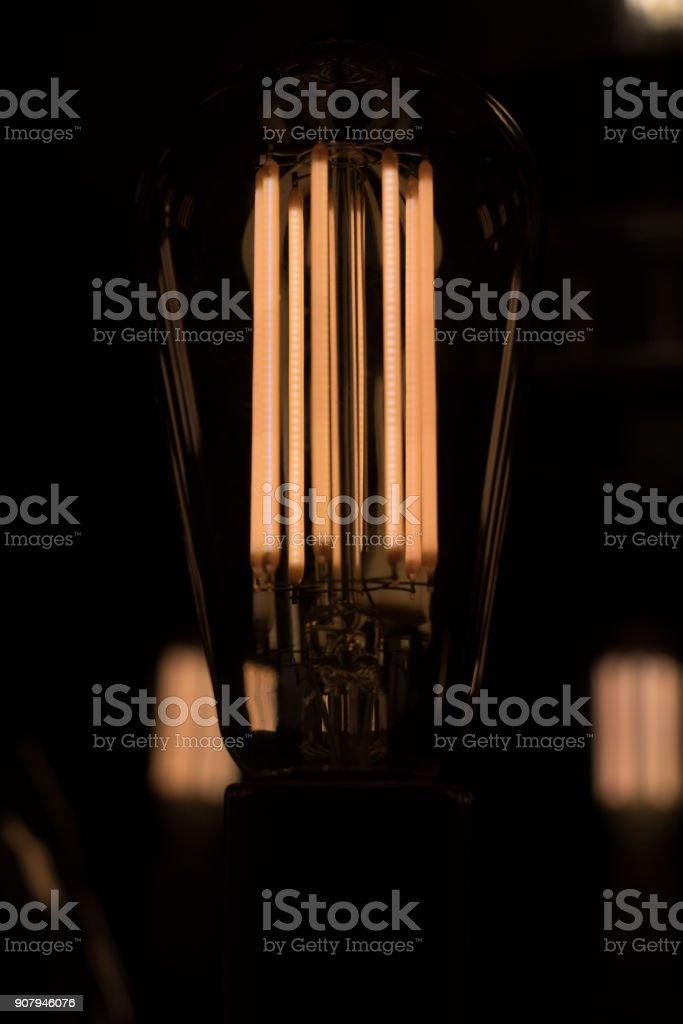 Retro light bulb glowing in the dark. stock photo