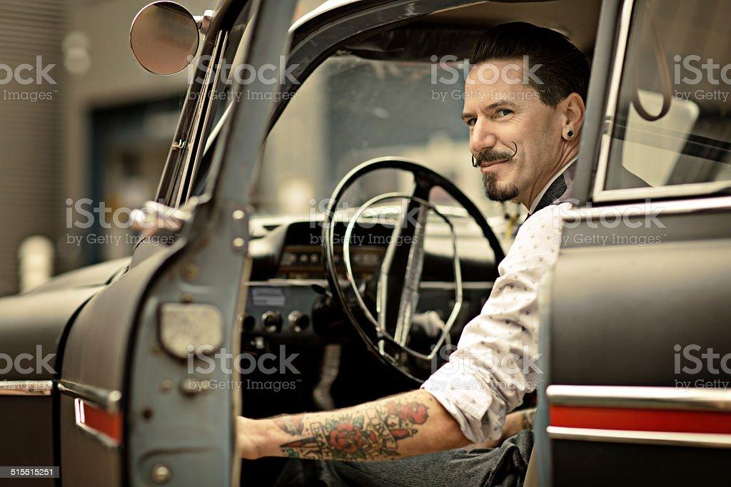 Homem retrô com longas moustaches sentado no carro - foto de acervo