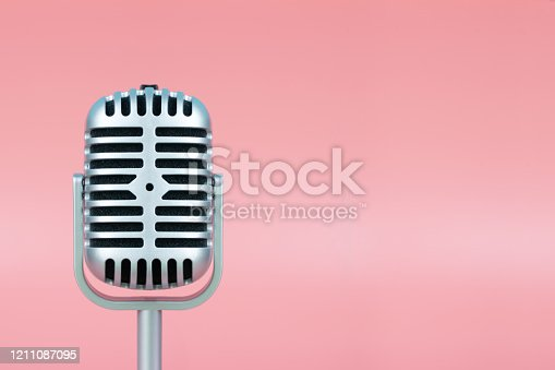 istock Retro microphone with copy space on pink background 1211087095