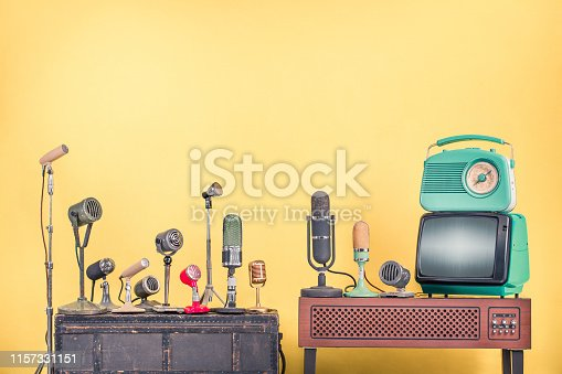 istock Retro microphones for interview or press conference, old mint green TV set and radio from 60s front yellow wall background. Vintage style filtered photo 1157331151