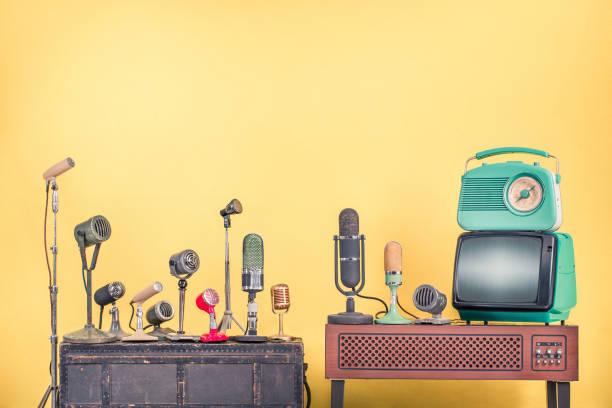 Retro-Mikrofone für Interview oder Pressekonferenz, altes mintgrünes TV-Gerät und Radio aus 60er Jahren vorderer gelber Wandhintergrund. Vintage-Stil gefiltertfoto – Foto