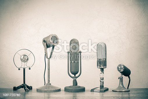 istock Retro microphones for press conference or interview. Vintage old style sepia photo 1051720782