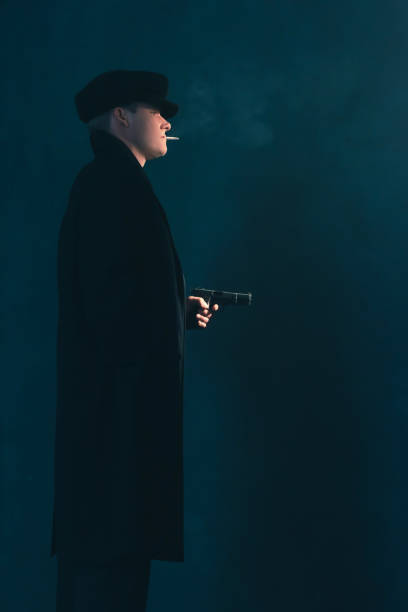 Retro mobster with cigarette shoots with gun. Side view. stock photo