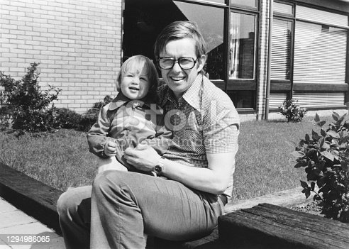 1975 vintage, seventies, retro monochrome portrait of father and daughter sitting in front of a house in the summer sun.