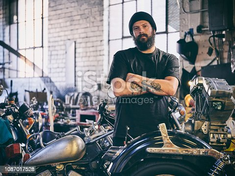A motorcycle mechanic working in an old fashioned retro style cycle repair shop.