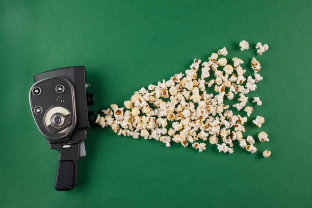 retro-filmkamera mit popcorn fliegen aus ihm heraus auf einem grünen hintergrund. - oscar filme stock-fotos und bilder