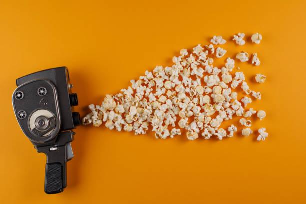 retro-filmkamera mit popcorn fliegen aus ihm heraus auf einem gelben hintergrund. - oscar filme stock-fotos und bilder